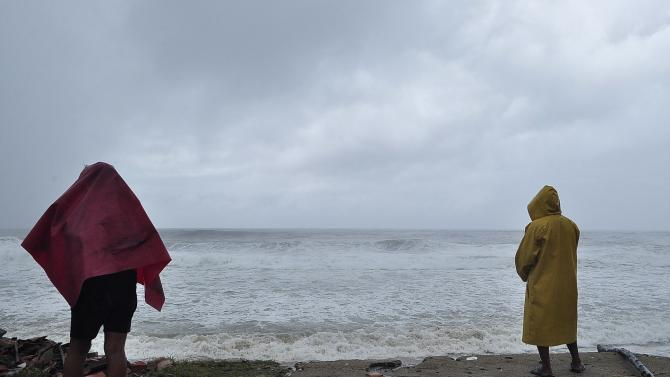 Residents stand near the beach as Tropical Storm Polo hits Coyuca de Benitez