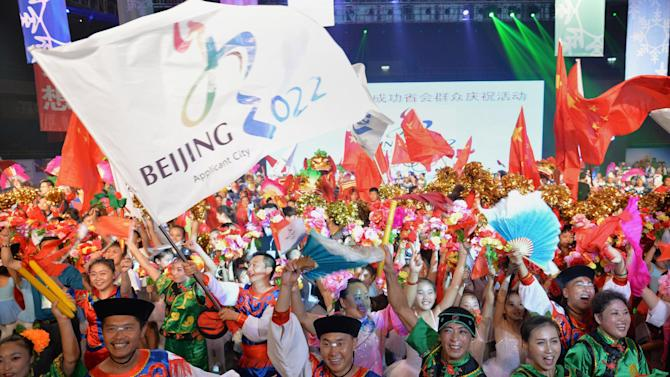 People wearing traditional costumes gather to celebrate as Beijing is announced as the host city for the 2022 Winter Olympic Games, in Shijiazhuang, the capital of northern China's Hebei province on July 31, 2015