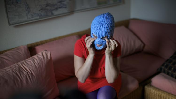 "A member of Russian punk band Pussy Riot, who gave only her stage name of Grelka, wears a blue balaclava as speaks to the media in Moscow, Tuesday, July 16, 2013. Russian provocateurs Pussy Riot are back in action, releasing their first music video since three members went to prison last year for a prank denouncing Vladimir Putin. The video shows band members in trademark bright-colored balaclavas and short skirts, cavorting and shrieking atop an oil rig. Backed by hectic guitar and a drum fusillade, they pour oil on a large photo of state oil giant Rosneft's chairman and liken Putin to an Iranian ayatollah. Pussy Riot member Grelka said after the video's Tuesday release that ""the main message is that Putin has spread the country's wealth among his friends."" (AP Photo/Alexander Zemlianichenko)"