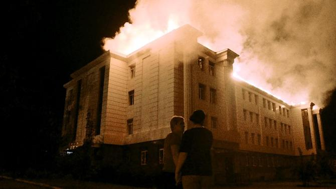 Bystanders watch a fire consuming a school in downtown Donetsk, eastern Ukraine on August 27, 2014 after it was hit by shelling