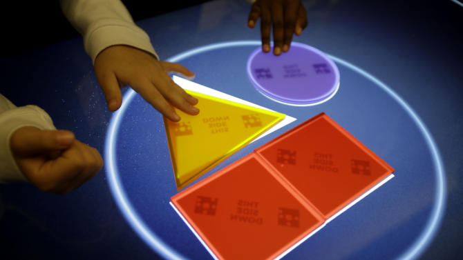 """Visitors to the new National Museum of Mathematics try out an interactive exhibit in New York, Monday, Dec. 17, 2012. The museum is aimed at kids aged 8 to 13, and curators have given the place a playground feel. The 40 exhibits include a """"wall of fire"""" made up of laser lights that teaches kids about geometry and a square-wheeled tricycle that still manages to produce a smooth ride thanks to a wavy track. (AP Photo/Seth Wenig)"""
