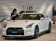 Customers check a Nissan vehicle at the company&#39;s showroom in Yokohama, suburban Tokyo on Thursday. Nissan has posted a 15% drop in quarterly profit as a strong yen and weak European market dent earnings, but Japan&#39;s second-biggest automaker says its full-year forecast is on track