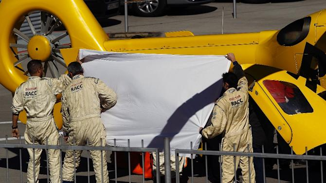 Fernando Alonso is shielded by teammates and medical staff as he is stretchered off after crashing during the Formula One pre-season fourth test day at the Circuit de Catalunya on February 21, 2015