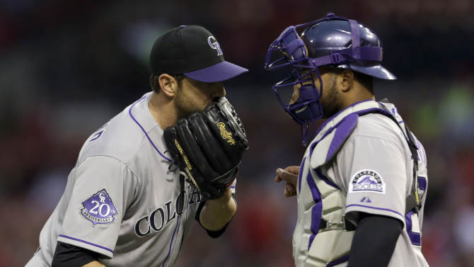 Colorado Rockies starting pitcher Jon Garland, left, talks with catcher Wilin Rosario during the second inning of a baseball game against the St. Louis Cardinals, Friday, May 10, 2013, in St. Louis. (AP Photo/Jeff Roberson)