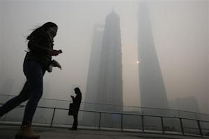 Residents wearing face masks use their mobile phones on a hazy day at the Pudong financial area in Shanghai