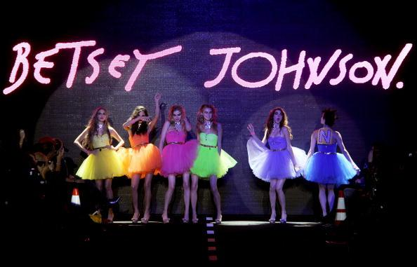 "For the finale a rainbow of puffy prom dresses dance their way out to the Beatles song ""Why Don't We Do it in the Road."" On their backs it spells out ""Ride On."""