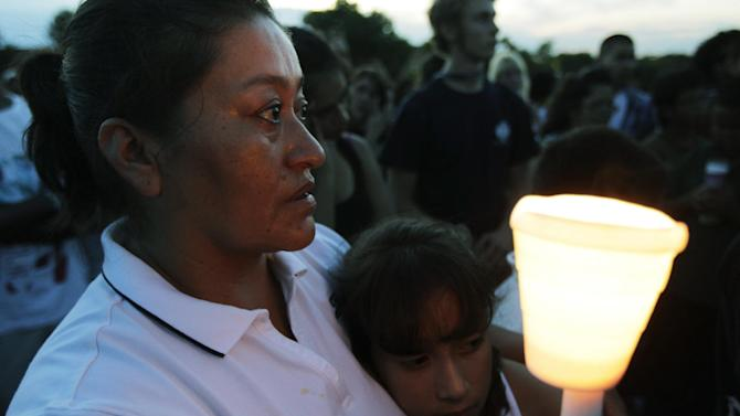 Maria Davila holds her daughter Alexia, 9, during a candle-light vigil, Friday, July 20, 2012, in Aurora, Colo., across the street from the movie theater where a gunman killed at least 12 people and wounded dozens of others Friday in one of the deadliest mass shootings in recent U.S. history. (AP Photo/Ted S. Warren)