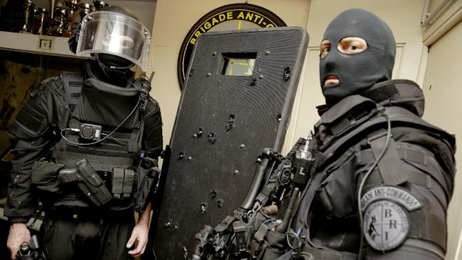 French police commandos with a bullet-hole riddled riot shield used during the assault at the Bataclan theatre in Paris during the November 13, 2015 terror attacks