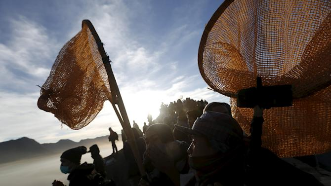 Villagers holds their nets as they wait for Hindu worshippers to throw their offerings into the crater during the Kasada Festival at Mount Bromo in Probolinggo