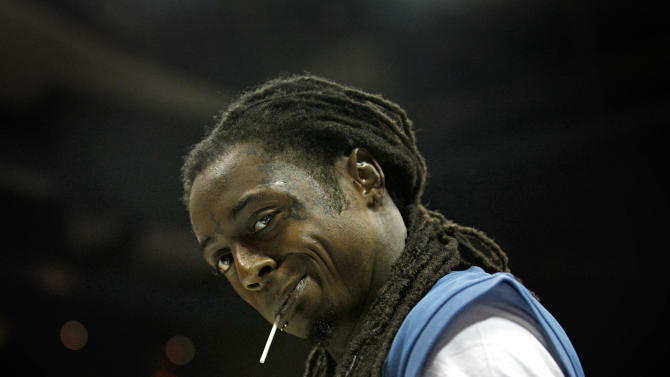 """FILE - This Oct. 7, 2011 file photo shows Hip Hop artist  Lil Wayne during halftime of Game 3 of the WNBA basketball finals between the Atlanta Dream and Minnesota Lynx, in Atlanta. The Rev. Al Sharpton says a meeting he held with PepsiCo Inc. officlals and members of Emmett Till's family was """"positive."""" Sharpton says in a statement PepsiCo officials apologized to the Till family at the Wednesday morning meeting at company headquarters in Purchase. PepsiCo and Lil Wayne ended their commercial relationship last week over vulgar lyrics the rapper included in a song that referenced Till, a black teen who became a civil rights icon after being killed while visiting Mississippi. (AP Photo/David Goldman, file)"""