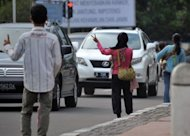 "Nuraini (C), a traffic ""jockey"", gestures to passing motorists in Jakarta. Carpooling rules designed to ease Jakarta's notorious traffic jams have turned hitch-hiking into a stable but illegal profession for Indonesia's poor"