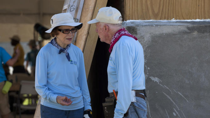 Former President Jimmy Carter, right, talks with his wife Rosalynn at a Habitat for Humanity project in Leogane, Haiti, Monday, Nov. 26, 2012.  The former president and former first lady were both taking an active part Monday in the construction of 100 one-room houses on about 14 acres which families will live in rent-free for five years and then pay a modest annual rent to the government. (AP Photo/Dieu Nalio Chery)