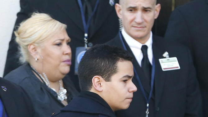 Justin Ramos, son of New York City police officer Rafael Ramos, right, arrives at Christ Tabernacle Church, in the Glendale section of Queens, wearing a police jacket before funeral services for his father, Saturday, Dec. 27, 2014, in New York. Ramos and his partner, officer Wenjian Liu, were killed Dec. 20 as they sat in their patrol car on a Brooklyn street. The shooter, Ismaaiyl Brinsley, later killed himself. (AP Photo/Julio Cortez)