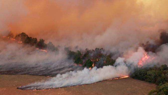 Flames burn near Highway 48 and HW 38 junction east of Drumright, Okla., on Saturday, Aug 4, 2012. Emergency management officials have ordered evacuations of homes in several areas as wildfires burn across the state. The Oklahoma Department of Emergency Services says no injuries have been reported. (AP Photo/Tulsa World, Tom Gilbert)