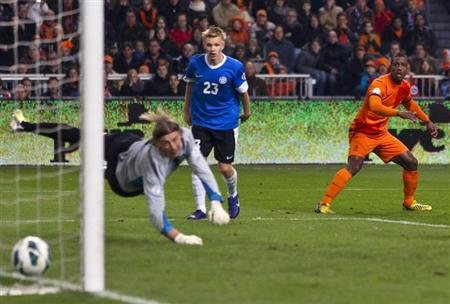 Ruben Schaken of the Netherlands (R) scores past goalkeeper Sergei Pareiko and Taijo Teniste of Estonia during their 2014 World Cup qualifying match in Amsterdam March 22, 2013. REUTERS/Michael Kooren