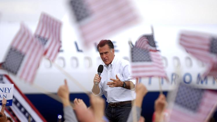 Flags wave as Republican presidential candidate, former Massachusetts Gov. Mitt Romney speaks at Pueblo Weisbrod Aircraft Museum in Pueblo, Colo., Monday, Sept. 24, 2012. (AP Photo/Bryan Oller)