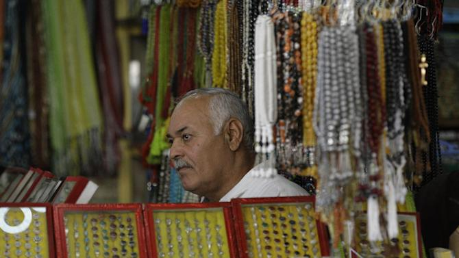 In this photo taken in Tuesday, Oct. 30, 2012,  shop owner, Yousif Jassim Mohammed sits as he waits for customers in Najaf, Iraq. The plunge in Iran's currency is proving bad for business in neighboring Iraq. Fewer Iranians are now able to afford visits to Shiite holy sites here and elsewhere in Iraq because each dollar or Iraqi dinar now costs roughly three times what it did as recently as last year. That has pushed the price of organized tours up sharply and made Iraqi merchants far less willing to accept rials as payment. (AP Photo/Khalid Mohammed)