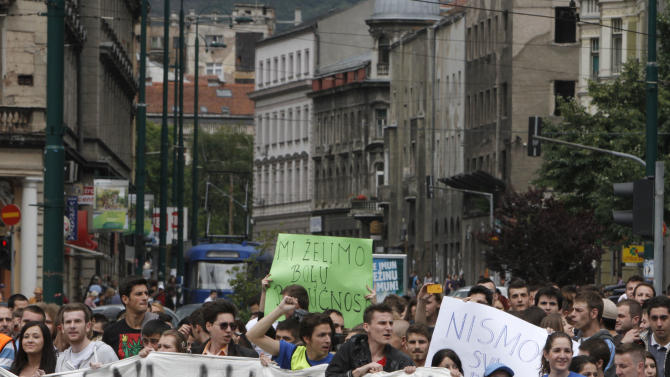 Bosnian students shout slogans during a protest in front of the Bosnian parliament, in Sarajevo, Friday, June 7, 2013. Bosnian students gathered again in the afternoon to continue their protest for the third day. After police ended the 12-hour siege laid by anti-government protesters to the Bosnian Parliament on Friday morning, crowds of mainly students gathered again in the afternoon to continue their protest for the third day. (AP Photo/Amel Emric)