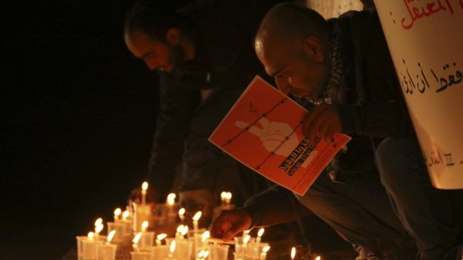 Activists light candles and observe a minute's silence during a vigil in solidarity with the detainees in Syrian prisons at Aleppo's Salaheddine neighborhood