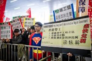 Demonstrators display placards against Hong Kong Chief Executive Leung Chun-ying prior to his policy address on January 16, 2013. Leung who won office after he campaigned promising to improve the lives of poor and middle-class citizens, was to give his first policy address amid discontent over issues including sky-high property prices and anti-Beijing sentiment