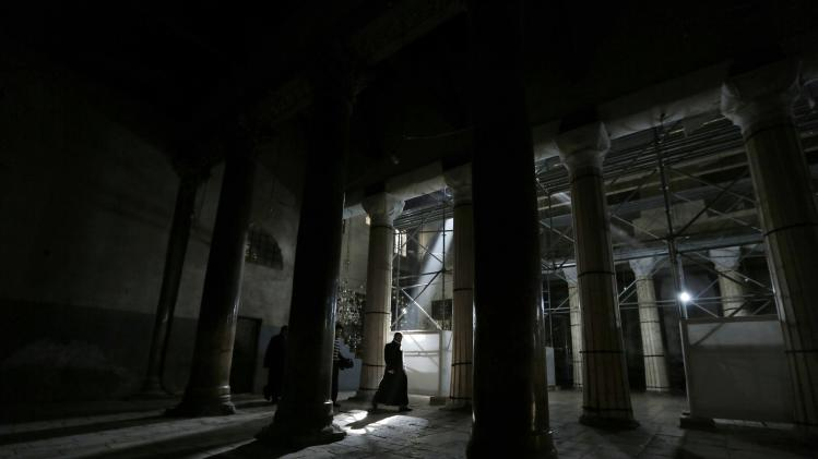 A priest walks near columns inside the Church of Nativity in Bethlehem