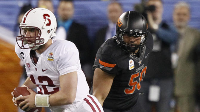 Stanford quarterback Andrew Luck (12) scrambles as Oklahoma State defensive end Jamie Blatnick pursues during the first half of the Fiesta Bowl NCAA college football game Monday, Jan. 2, 2012, in Glendale, Ariz. (AP Photo/Matt York)