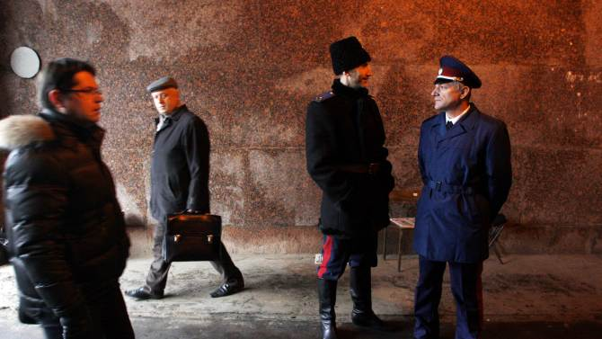 Two Russian Cossacks, right, watch pedestrians passing by as they patrol Belorussky railway station in downtown Moscow, Russia, Tuesday, Nov. 27, 2012. Renowned for their sword-fighting prowess and anti-Semitism in czarist Russia, the Cossacks are taking on new foes: beggars, drunks, unlicensed traders and improperly parked cars. (AP Photo/Pavel Golovkin)