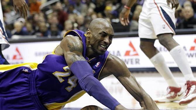 Los Angeles Lakers guard Kobe Bryant (24) loses control of the ball as he drives to the basket  in the second half of an NBA basketball game against the Atlanta Hawks in Atlanta Wednesday, March 13, 2013. (AP Photo/John Bazemore)