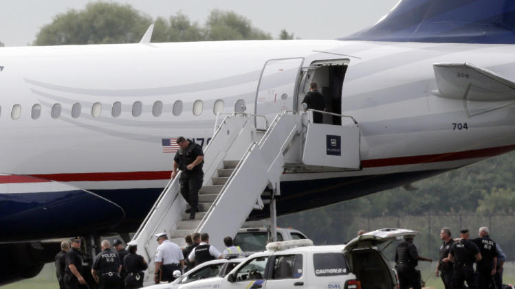 Law enforcement officials work around a US Airways flight at Philadelphia International Airport, after the plane returned to the airport, Thursday, Sept. 6, 2012, in Philadelphia. A security scare that prompted authorities to recall an airborne U.S. flight was the result of an apparent hoax, police said Thursday. (AP Photo/Matt Rourke)