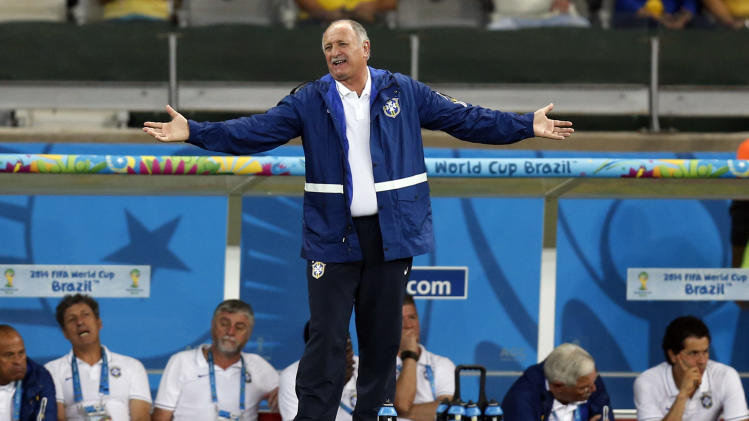 Brazil's coach Luiz Felipe Scolari spreads his arms as he watches the World Cup semifinal soccer match between Brazil and Germany at the Mineirao Stadium in Belo Horizonte, Brazil, Tuesday, July 8, 2014