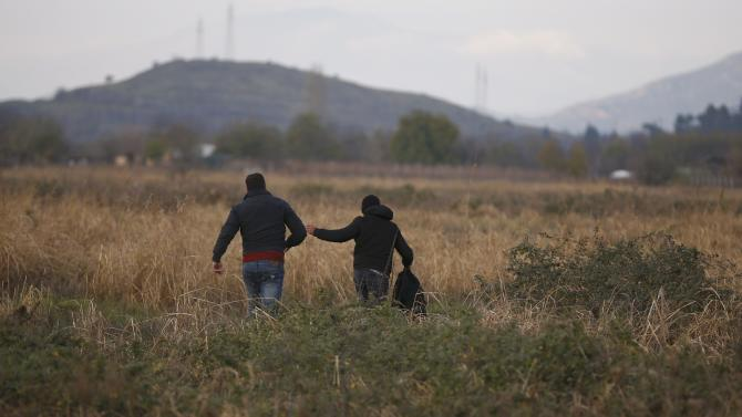 Migrants run through a field after crossing the border from Greece into Macedonia, near Gevgelija
