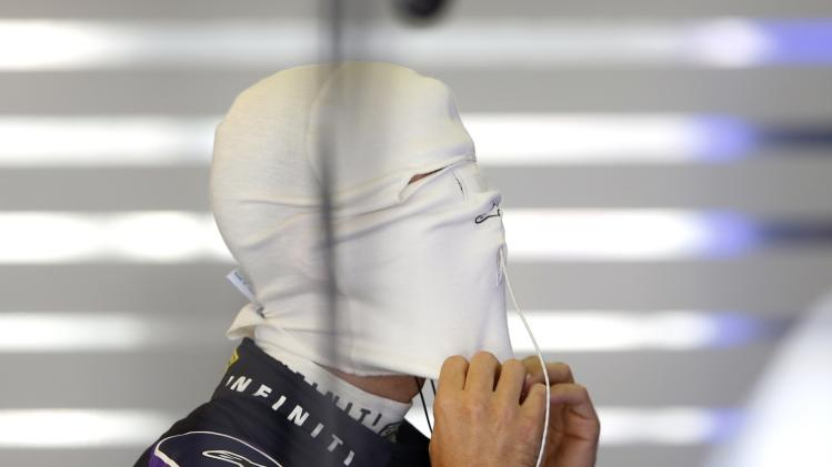 Red Bull Formula One driver Vettel of Germany adjusts his balaclava before the second practice session of the Hungarian F1 Grand Prix at the Hungaroring circuit
