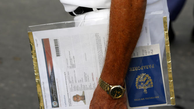 "A man applying for a U.S. visa holds his U.S. Department of State forms and Cuban passport as he waits in line outside the U.S. Interests Section in Havana, Cuba, Wednesday, July 1, 2015. President Barack Obama announced Wednesday that the U.S. and Cuba will reopen their embassies in Havana and Washington, heralding a ""new chapter"" in relations after a half-century of hostility. (AP Photo/Desmond Boylan)"
