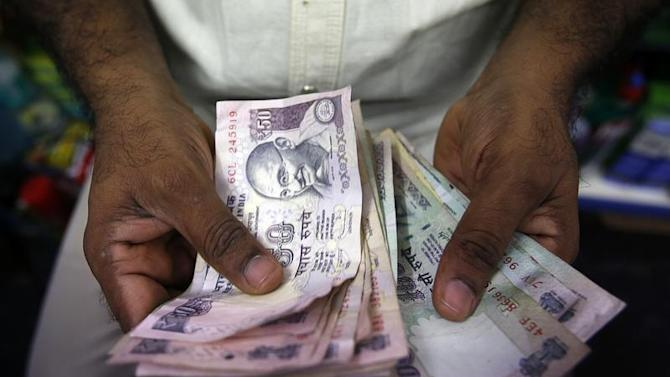 A private money trader counts Indian Rupee currency notes at a shop in Mumbai