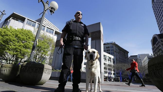 """Seattle Police K9 officer Craig Williamson stands with his explosives detection dog, """"Dennis"""" as he patrols downtown Seattle, Monday, April 15, 2013, in reaction to explosions at the Boston Marathon finish line earlier in the day. A Seattle Police blog posting said that although there was no indication of a direct threat to Seattle, officers would be increasing patrols and activity around the city. (AP Photo/Ted S. Warren)"""