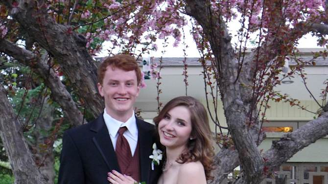 This April 2012 photo released by Patricia Weintraub shows Amy Weintraub, right, and Luke Siddens posing for a picture for the Poudre High School prom in Fort Collins, Colo. Luke used a cell phone photo of Amy's dress to make sure his tie was in a matching shade of brown. (AP Photo/Patricia Weintraub)