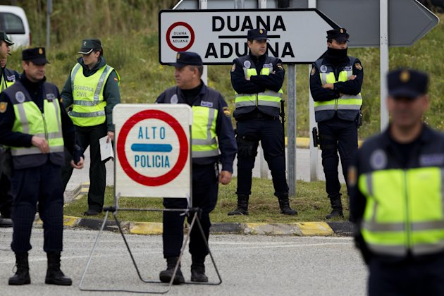 Police officers stand guard in a checkpoint near to the border of Spain and France in La Jonquera, Girona, Spain, Saturday, April 28, 2012. Spain has temporarily restored border checks in its northeast and at two major airports in a bid to stop protesters entering the country ahead of a European Central Bank meeting in Barcelona. Spanish authorities early Saturday suspended the Schengen Treaty which allows unrestricted travel inside member nations, and imposed controls at six border crossings with France and at Barcelona and Gerona international airports. (AP Photo/Emilio Morenatti)