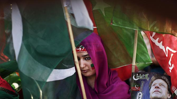 """A Pakistani supporter of former cricket star-turned-politician, and leader of Pakistan Tehreek-e-Insaf party, Imran Khan, takes part during a rally in Khan's support in Islamabad, Pakistan, Thursday, May 9, 2013. Pakistan is scheduled to hold parliamentary elections on May 11, the first transition between democratically elected governments in a country that has experienced three military coups and constant political instability since its creation in 1947. The parliament's ability to complete its five-year term has been hailed as a significant achievement. Headband reads, """"Pakistan Tehreek-e-Insaf"""".  (AP Photo/Muhammed Muheisen)"""