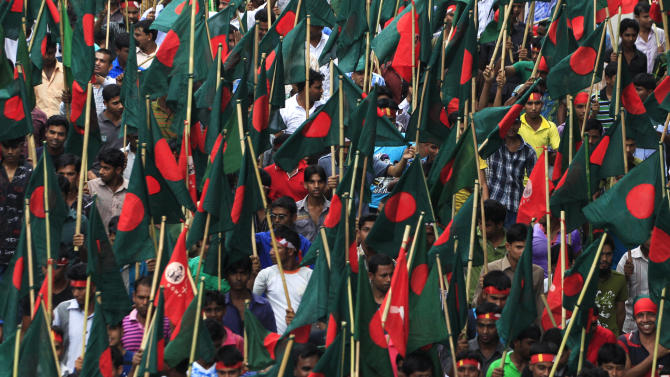 Protesters carry the national flags and shout slogans during a May Day rally on Wednesday May 1, 2013 in Dhaka, Bangladesh. Thousands of workers paraded through central Dhaka on May Day to demand safer working conditions and the death penalty for the owner of a building housing garment factories that collapsed last week in the country's worst industrial disaster, killing at least 402 people and injuring 2,500. (AP Photo/Ismail Ferdous)