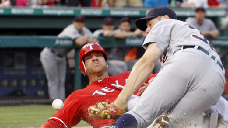 ALTERNATE CROP - Texas Rangers Chris Davis, left, slides into Detroit Tigers third baseman Don Kelly (32) forcing him to drop the ball at home plate to score a run during the third inning of a baseball game at Rangers Ballpark in Arlington, Texas, Wednesday June 8, 2011. (AP Photo/Sharon Ellman)