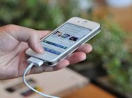 A customer looks at an Apple iPhone 4S in 2011. Mobile phone manufacturers, responding to consumer and regulatory pressure, are using fewer toxic substances in their products, researchers in the United States said Wednesday
