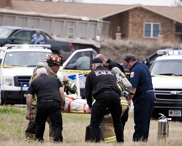Emergency personnel carry the driver of a black Cadillac with Colorado plates who was involved in a high speed chase and shootout with police in Decatur, Texas, Thursday, March 21, 2013. The driver le