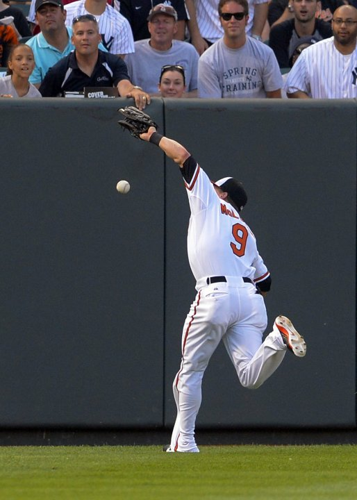 Baltimore Orioles left fielder Nate McLouth can't catch up to a fly ball during their MLB American League baseball game in Baltimore