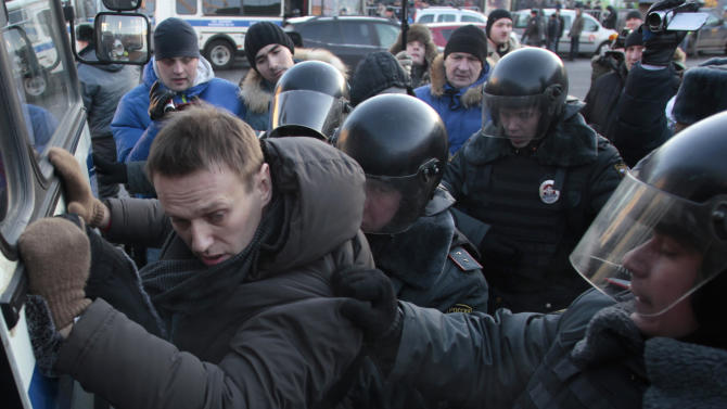 FILE - In this Saturday, Dec. 15, 2012 file photo police officers detain opposition leader Alexei Navalny during an unauthorized rally in Lubyanka Square in Moscow. Navalny, who helped organized the largest anti-Kremlin rallies in Russia's post-Soviet history, was charged with fraud and money-laundering Thursday. (AP Photo/Pavel Golovkin, File)