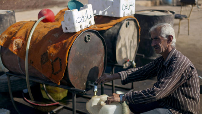 In this Wednesday, Nov. 7, 2012 photo, a Syrian man fills a plastic container with diesel fuel from a street vendor in the Syrian village of Atmeh, near the Turkish border with Syria. The civil war raging through Syria has battered much of the country's economy, making life harder for poor Syrians who struggled even before fighting broke out. Those struggles are clear even in places spared large scale destruction, such as Atmeh, which abuts Syria's northern border with Turkey, and other nearby villages.(AP Photo/Khalil Hamra)