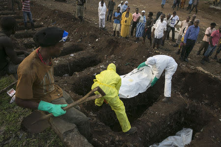 Grave digger watches as health workers carry the body of an Ebola victim for burial at a cemetery in Freetown