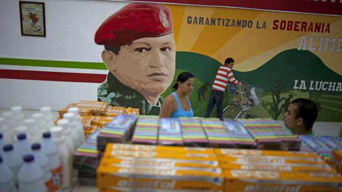 In this April 8, 2013 photo, a mural of Venezuela's late President Hugo Chavez adorns a supermarket wall as customers shop in Maracay, Venezuela. Outside Venezuela's capital, power outages, food shortages and unfinished projects abound; important factors heading into Sunday's election to replace Chavez, who died last month after a long battle with cancer. Maduro, Chavez's hand-picked successor, is favored to win, largely on the strength of Chavez's generous anti-poverty programs. But recent polls show that support for Maduro may be eroding. (AP Photo/Ramon Espinosa)