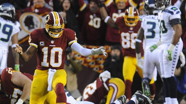 Washington Redskins quarterback Robert Griffin III reacts to a touchdown by running back Evan Royster, background, during the first half of an NFL wild card playoff football game against the Seattle Seahawks in Landover, Md., Sunday, Jan. 6, 2013. (AP Photo/Richard Lipski)