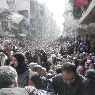 Residents wait to receive food aid distributed by the U.N. Relief and Works Agency (UNRWA) at the besieged al-Yarmouk camp, south of Damascus