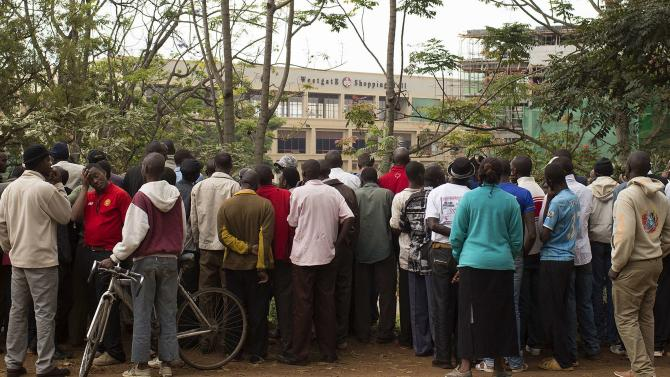 Onlookers stand along the road and look from a distance at Westgate Shopping Centre, where gunmen are holding hostages, in Nairobi